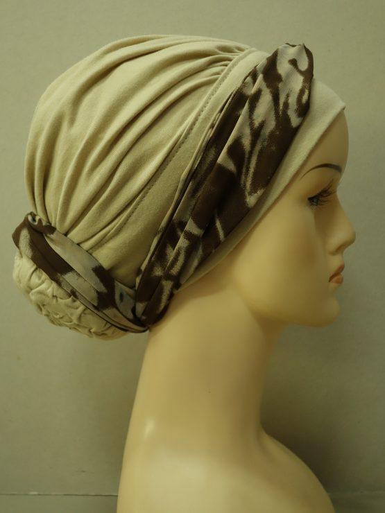 Beżowy bawełniany drapowany turban z kokiem i dekoracją z jedwabnej żorżety.