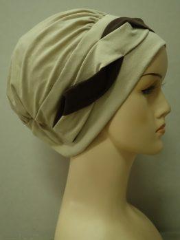 Beżowa modna czapka z plecioną dekoracją.