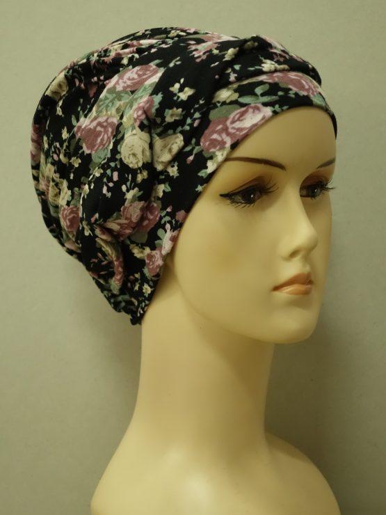 Czarna modna czapka w z plecioną dekoracją w kwiaty.